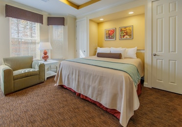 Bedroom with three windows and seating area in a presidential villa at Fox River Resort in Sheridan, Illinois