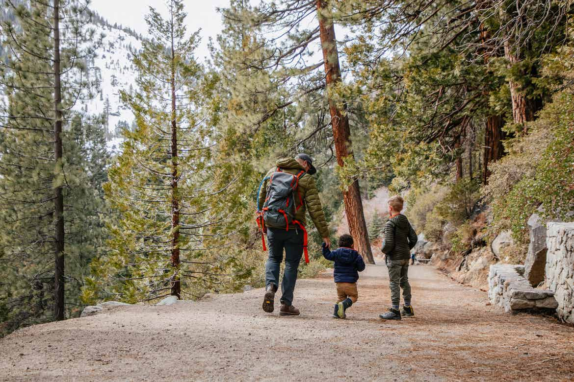A family walks through Emerald Bay State Park with a gorgeous forest as a backdrop.