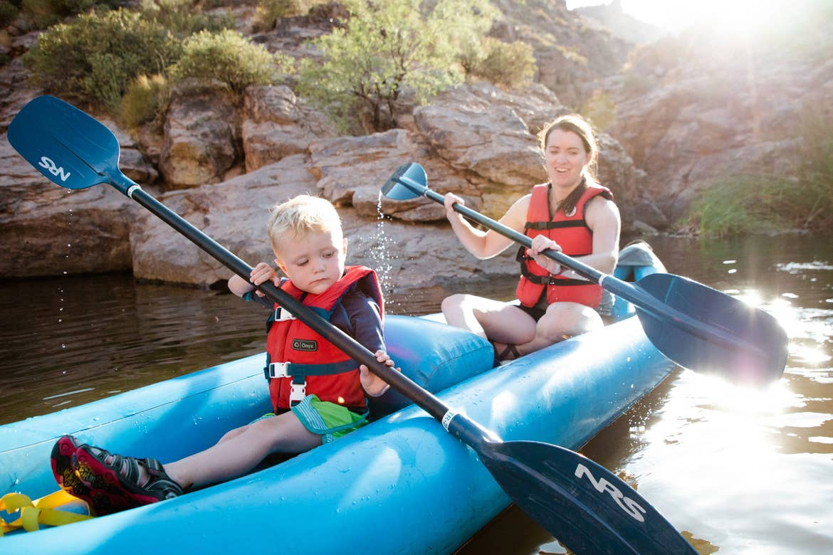 Author Jessica Averett (right) and her son (left) wear life jackets as they paddle their kayak in the water.
