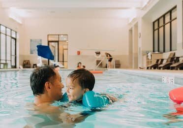 Adult and child swimming in indoor pool at Williamsburg Resort.