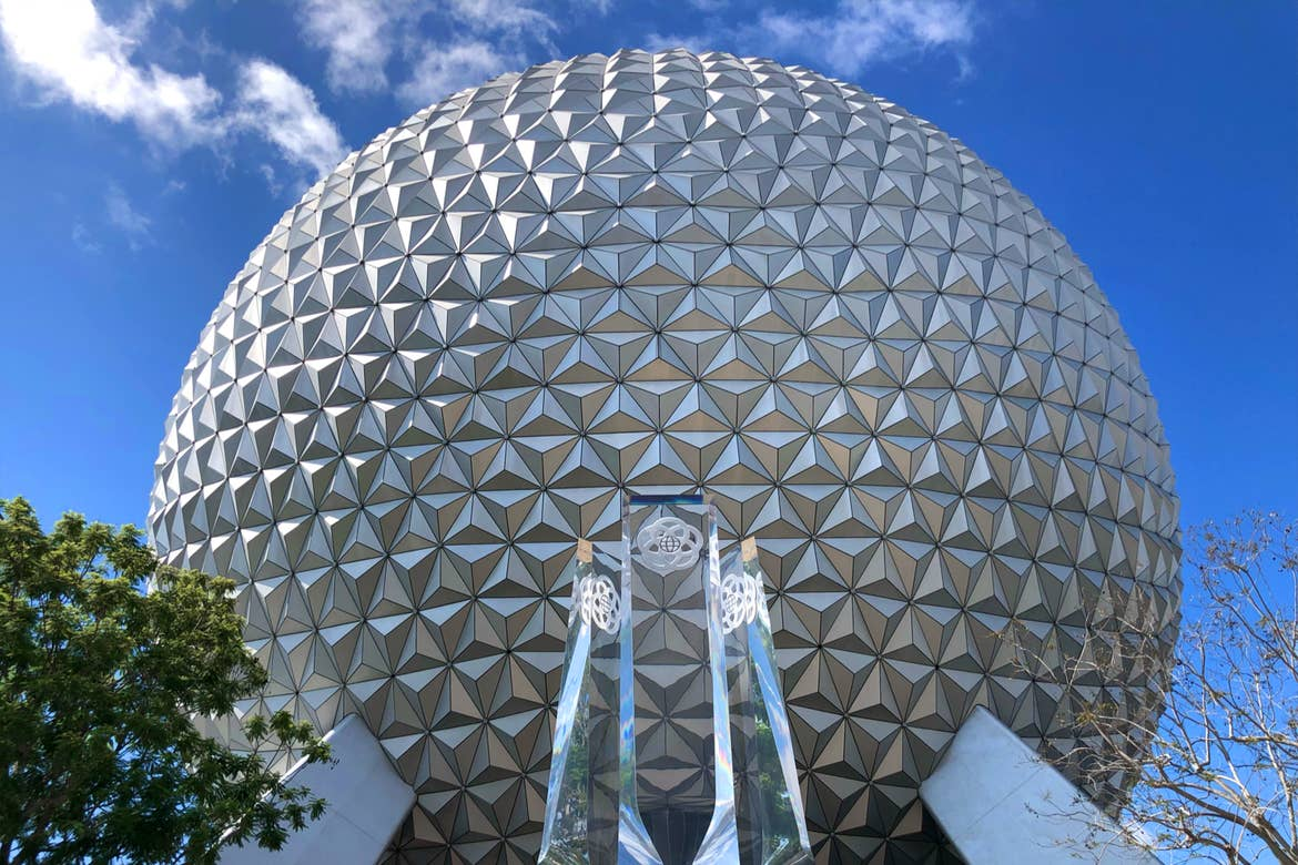 The Geosphere that holds Spaceship Earth at Epcot stands under a blue sky with new acrylic pylons representing the past, present and future of Epcot.