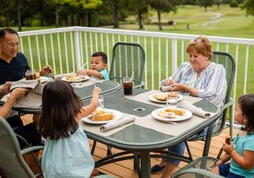 Family of six eating outdoors at The Grill on the Green at Holiday Hills Resort in Branson, Missouri.