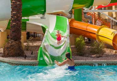Young girl sliding down a water slide into the pool at Scottsdale Resort in Arizona