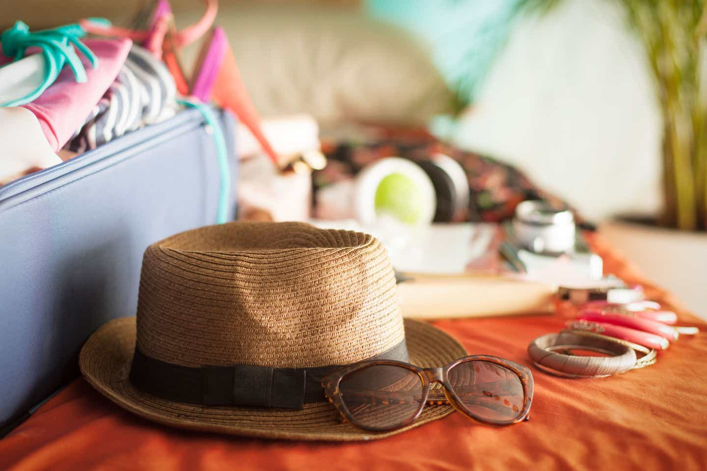 Various items, including a straw fedora, sunglasses, and wooden bangle bracelets, are placed outside of a navy suitcase on an orange bedspread.