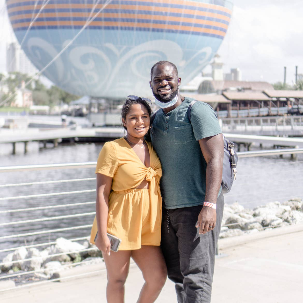 Author, Kimberly Gelin (left), poses with her husband in front of the 'Aerophile – The World Leader in Balloon Flight' at Disney Springs in Walt Disney World Resort.