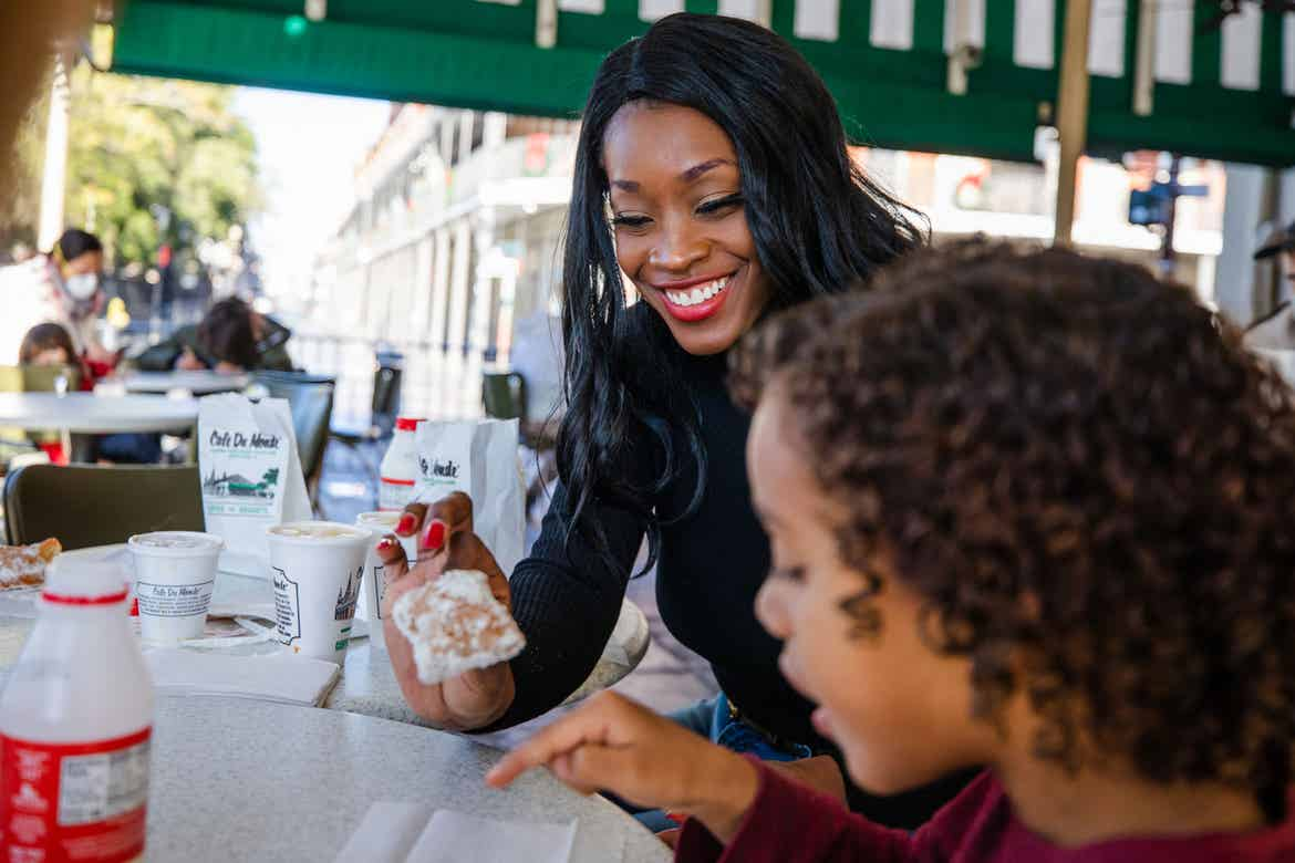 Featured Contributor, Sally Butan of @butanclan (back) and her son, Alex (front), sit under the green canopy outside Cafe Du Monde eating powdery beignets at a white table in New Orleans, Louisiana.