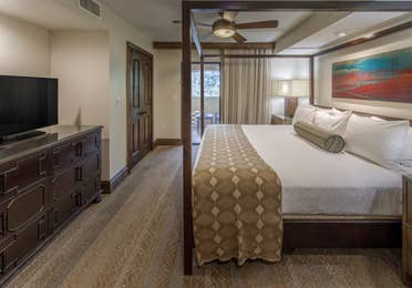 Bedroom with canopy bed and door leading to a patio in a Two-Bedroom Signature Collection villa at Scottsdale Resort in Arizona