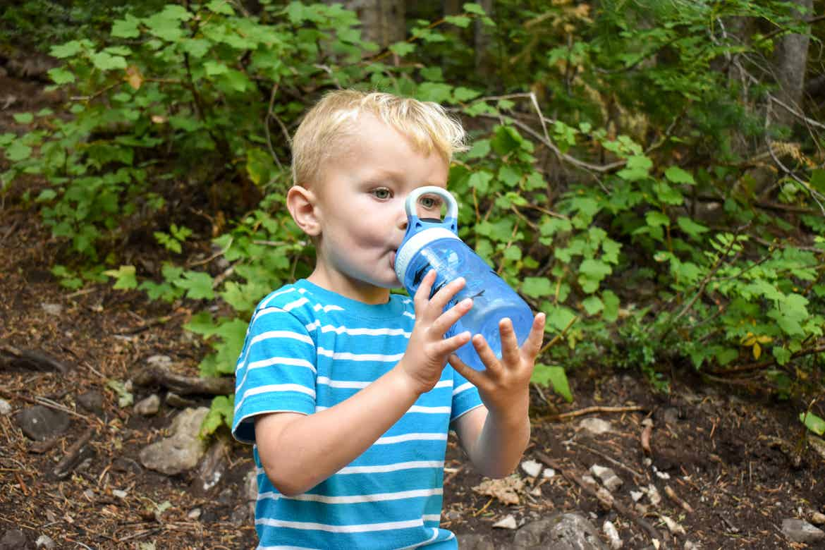 Jessica's son drinking from a water bottle during a hike break
