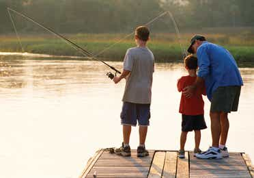 Family fishing on a dock at the Holiday Hills Resort in Branson Missouri.
