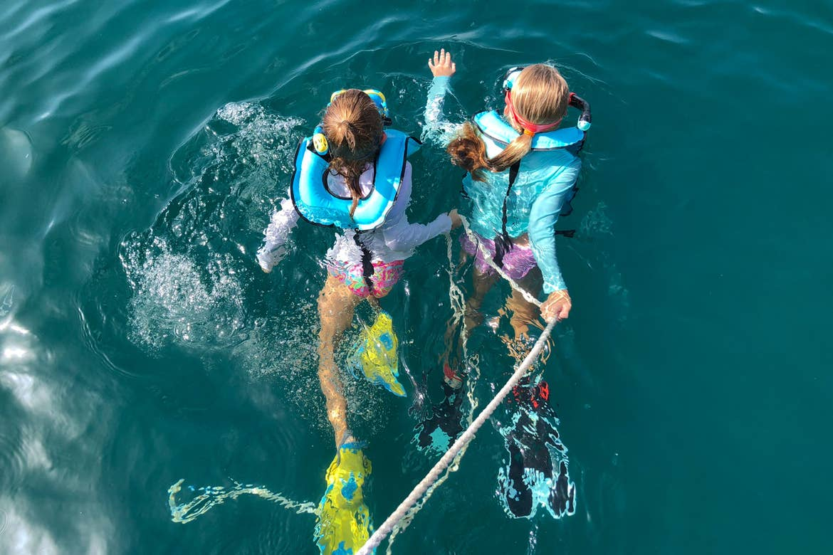 Featured Contributor, Chris Johnston's two daughters, Kyler (left) and Kyndall (right), wear multi-colored snorkel gear while holding onto a rope in the ocean.