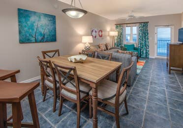 Dining room table with six chairs and view of living room in a two-bedroom villa at Panama City Beach Resort