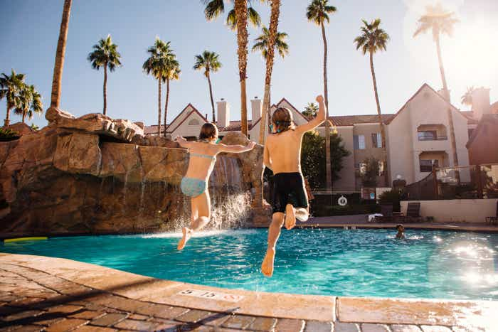 The Haby kids jump into one of the heated pools of our Desert Club Resort located in Las Vegas, Nevada wearing swimsuits and goggles.