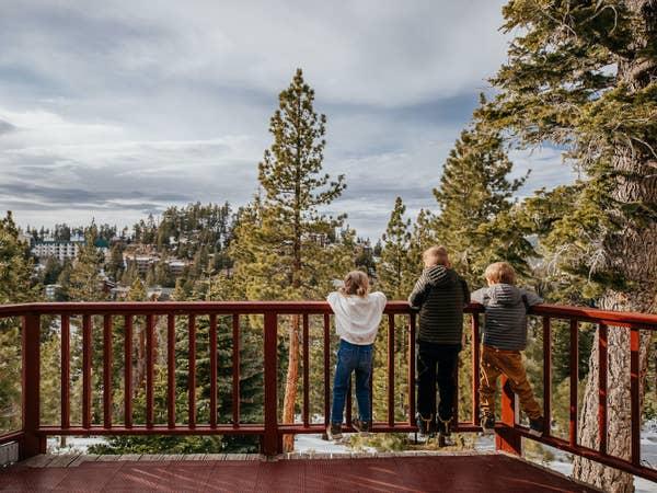 Three kids enjoying view of trees at Tahoe Ridge Resort in Stateline, Nevada.