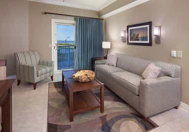 Living room with couch, accent chair, and access to balcony in a two-bedroom villa at Galveston Beach Resort