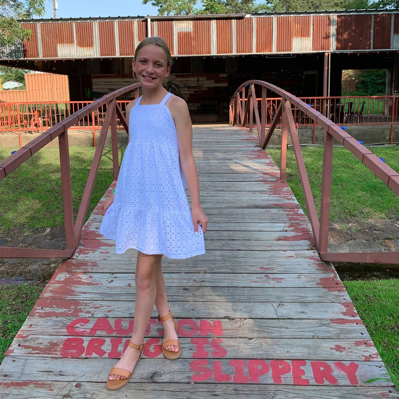 A caucasian girl wears a white dress near a bridge.