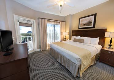 Master bedroom with king bed, flat screen TV, and large window in a one-bedroom villa at Galveston Beach Resort