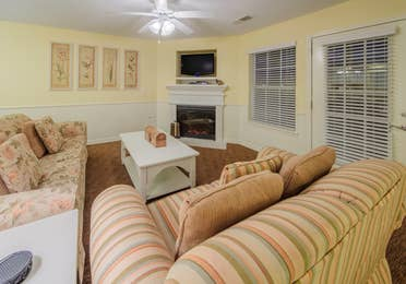 Living room with two couches, fireplace, and flat screen TV in a Presidential two-bedroom villa at Ozark Mountain Resort in Kimberling City, Missouri