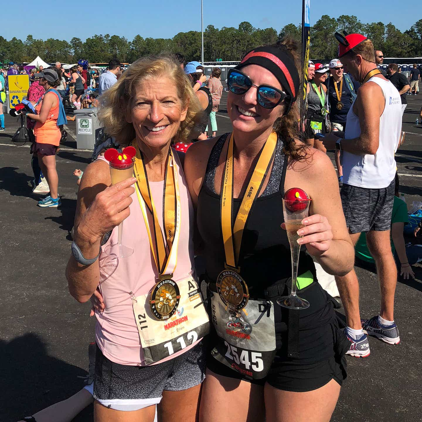Co-author, Christine (right), wears a medal, black tank top and shorts while holding a Mickey drink with her mom (left).