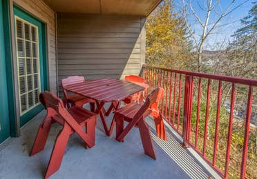 Balcony with table and chairs overlooking nature during the fall season in a two bedroom villa at Oak n' Spruce Resort in South Lee, Massachusetts