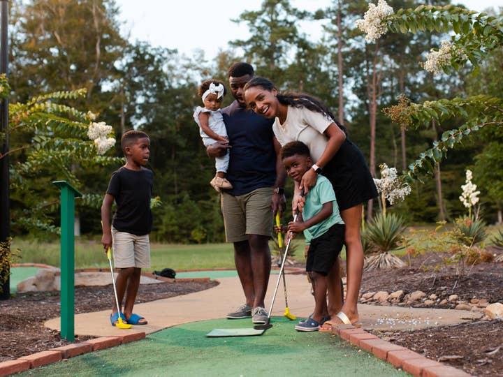 Family playing mini-golf.