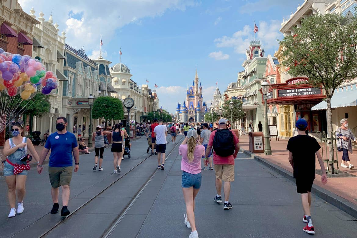 Several guests wearing safety masks walk up and down Main Street USA at the Magic Kingdom at Walt Disney World Resort as Cinderella's Castle stands in the distance under a cloudy blue sky.