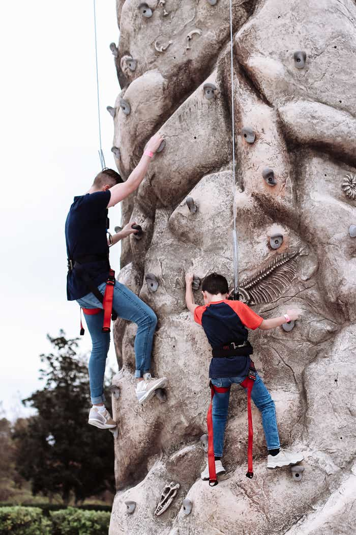 Mia's husband and son climbing a rock wall