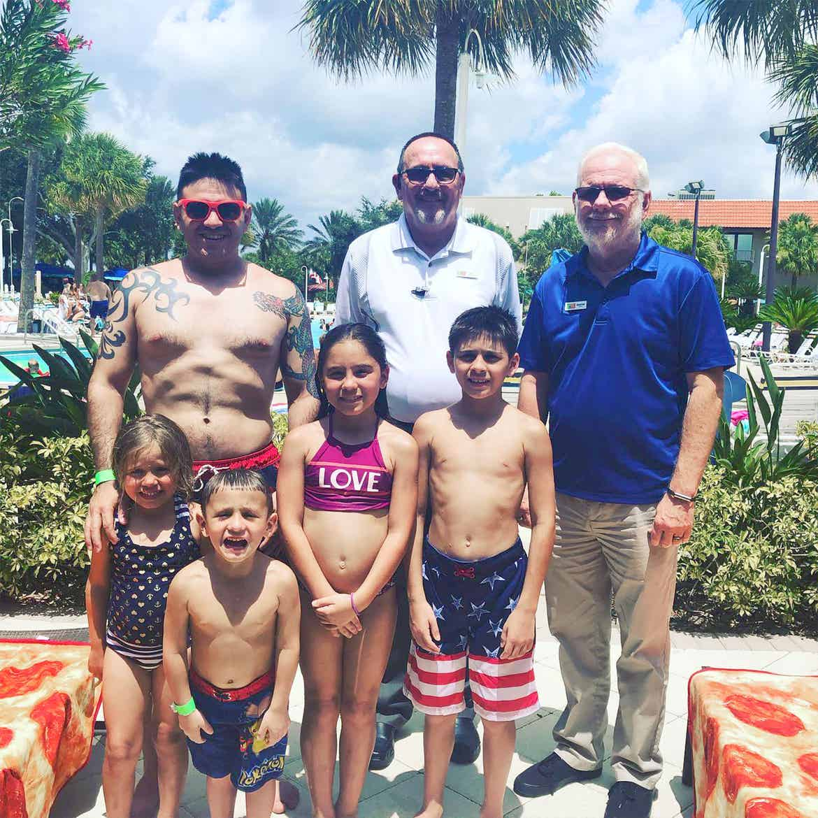 Featured Member, Sara Perezes family stands with HICV Team Members outside of our River Island pool.