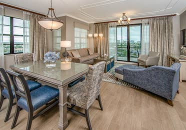 View of dining room table with six chairs, full living room, and access to furnished balcony in a three-bedroom villa at Sunset Cove Resort in Marco Island, Florida