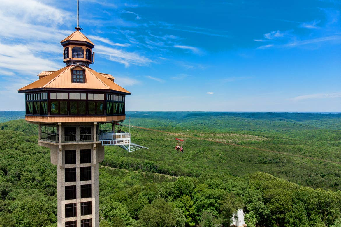 Inspiration Tower — the highest point in Southwest Missouri, has two zip-liners making their way down the zipline.