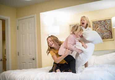 Three children laughing and having a pillow fight on the bed.