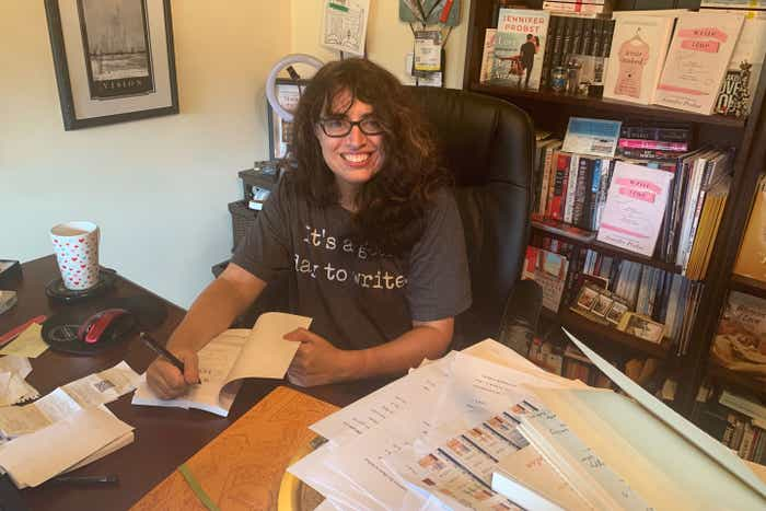 Author, Jennifer Probst, wears her glasses and a grey shirt while writing a book on her desktop.