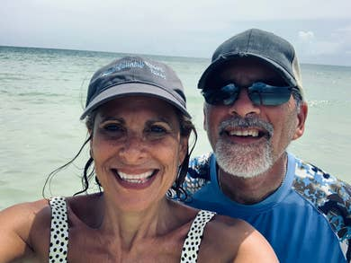 Beach selfie of Denise and CJ with the ocean in the background.