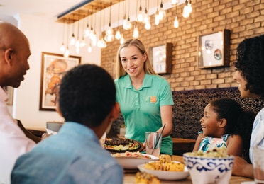 Waitress bringing a plate of food to a family in a restaurant