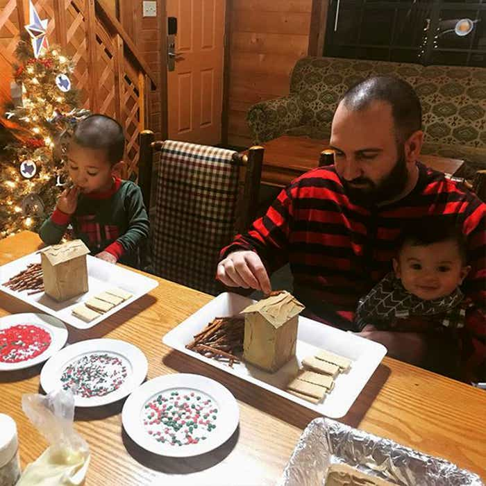 Guests dressed and holiday jammies sit at our Holly Lake resort kitchen table making gingerbread houses.
