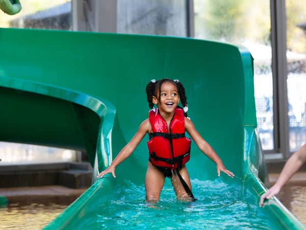 Small child coming out of waterslide at The Waterpark at The Villages at Villages Resort in Flint, Texas.
