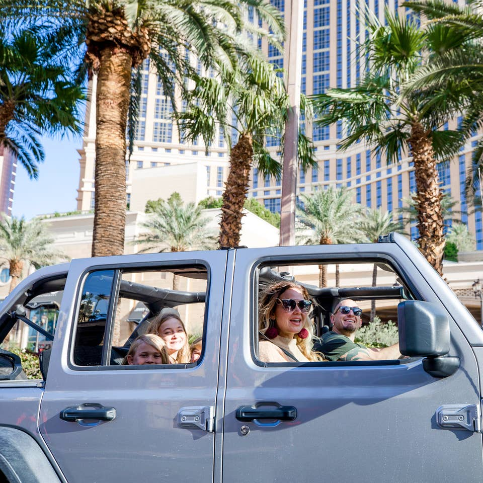 A man drives a silver Jeep Wrangler with one female passenger and three children in the back though the Las Vegas strip with the roof shell off.