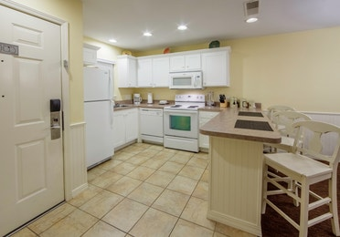 Kitchen with fridge, dishwasher, oven, microwave, and sink in a Presidential two-bedroom villa at Ozark Mountain Resort in Kimberling City, Missouri