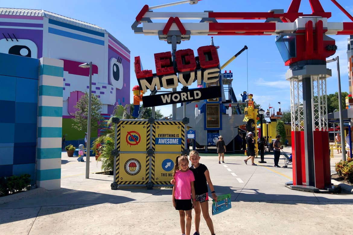 Two young girls stand under a sign made of LEGO's that reads, 'LEGO Movie World.'