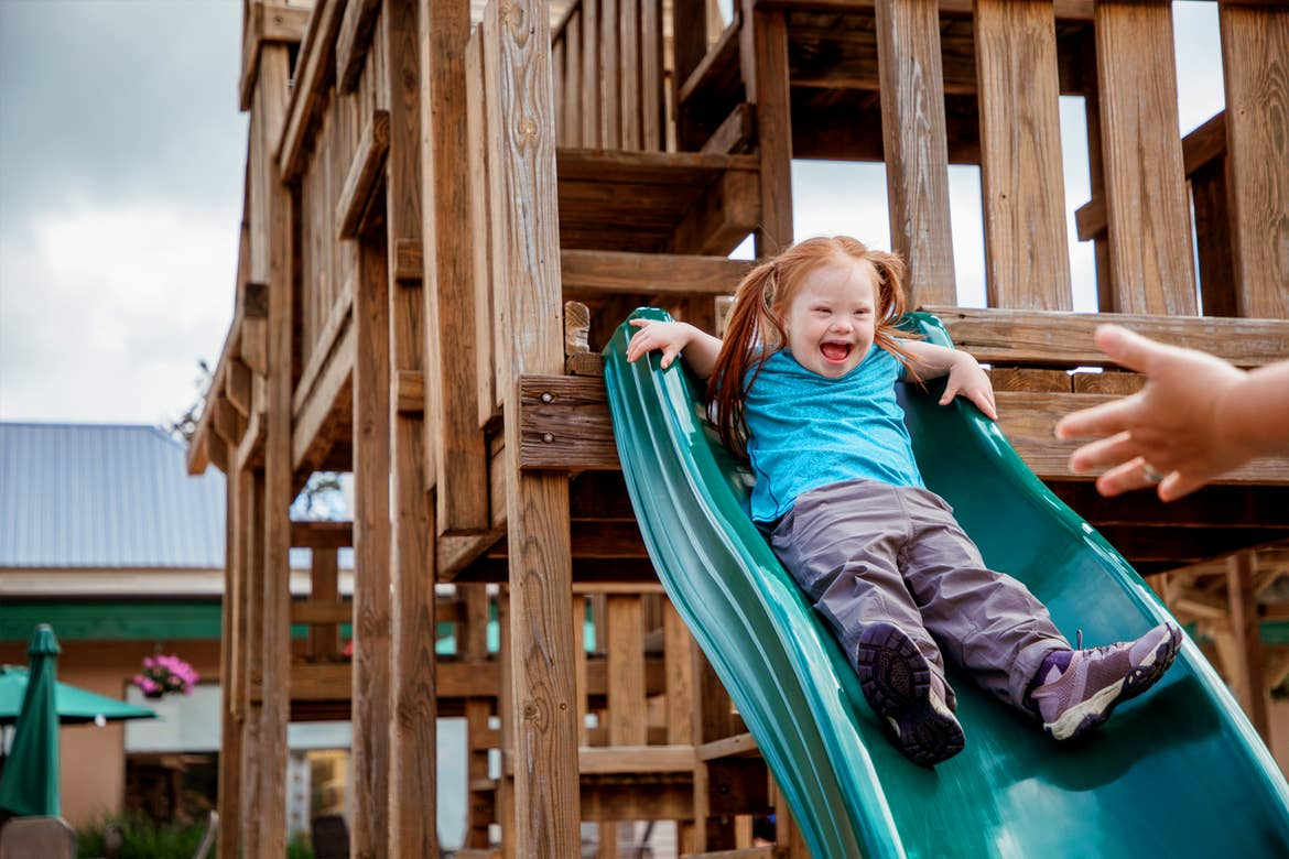 A young, caucasian girl with red hair, an aqua shirt and khaki-colored pants slides down a wooden playground slide outdoors.