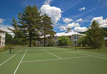 Tennis court surrounded by beautiful trees and buildings of the Oak n' Spruce Resort in South Lee, Massachusetts