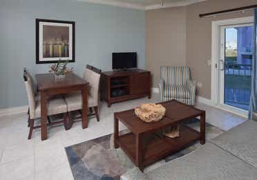 Living room with couch, flat screen TV, and dining table with four chairs in a two-bedroom villa at Galveston Beach Resort