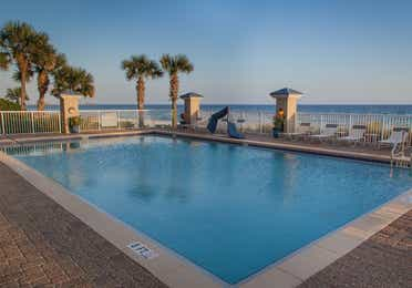 Outdoor pool surrounded by palm trees with beachfront view at Panama City Beach Resort in Florida.