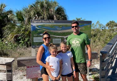 A caucasian family of four stand in front of a trail map with Palm Trees in the back.