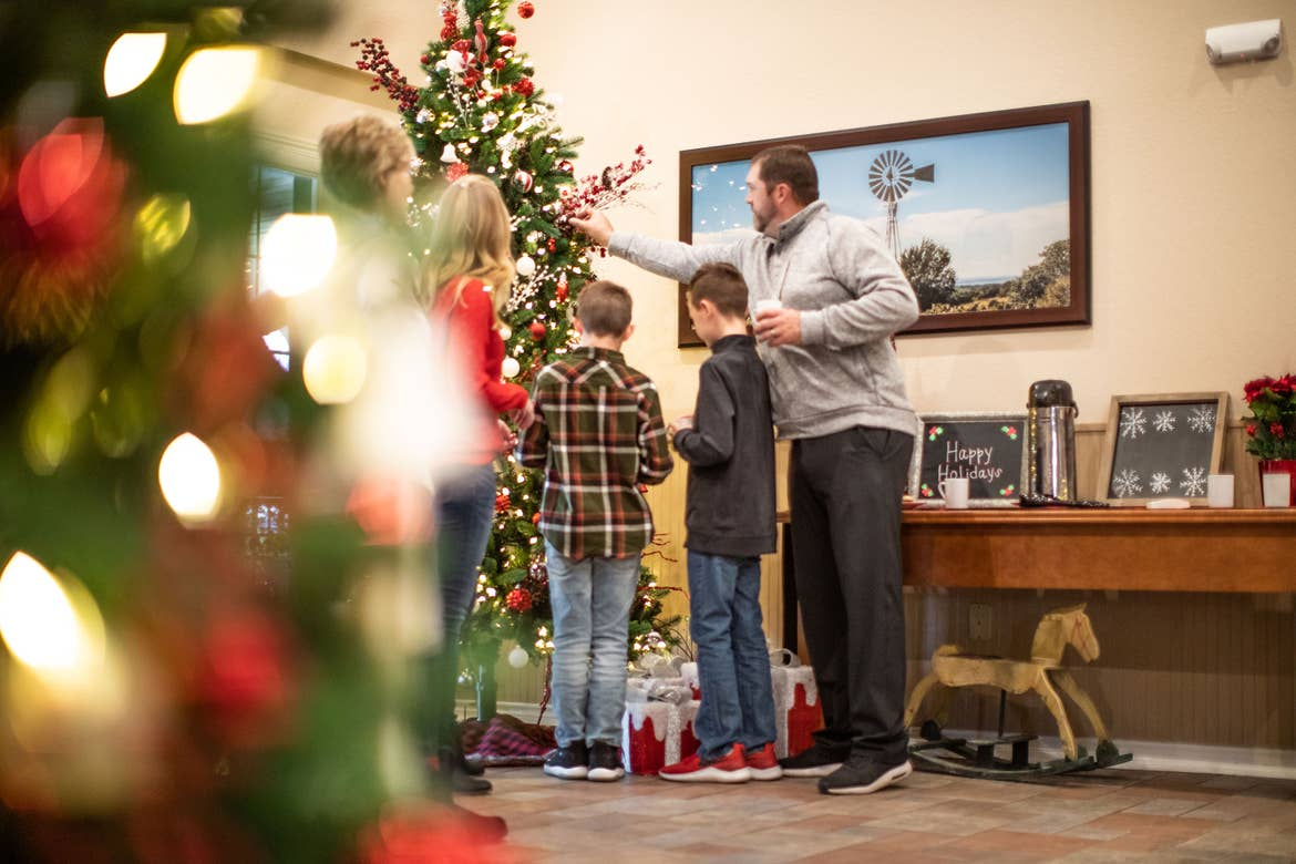 Author, Amanda Nall (left), and her family help with decorating holiday decor while drinking hot cocoa.
