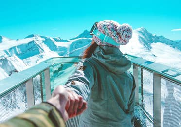 A woman holds a man's hand while wearing winter apparel and ski goggles looking off at snowcapped mountains under a blue sky.