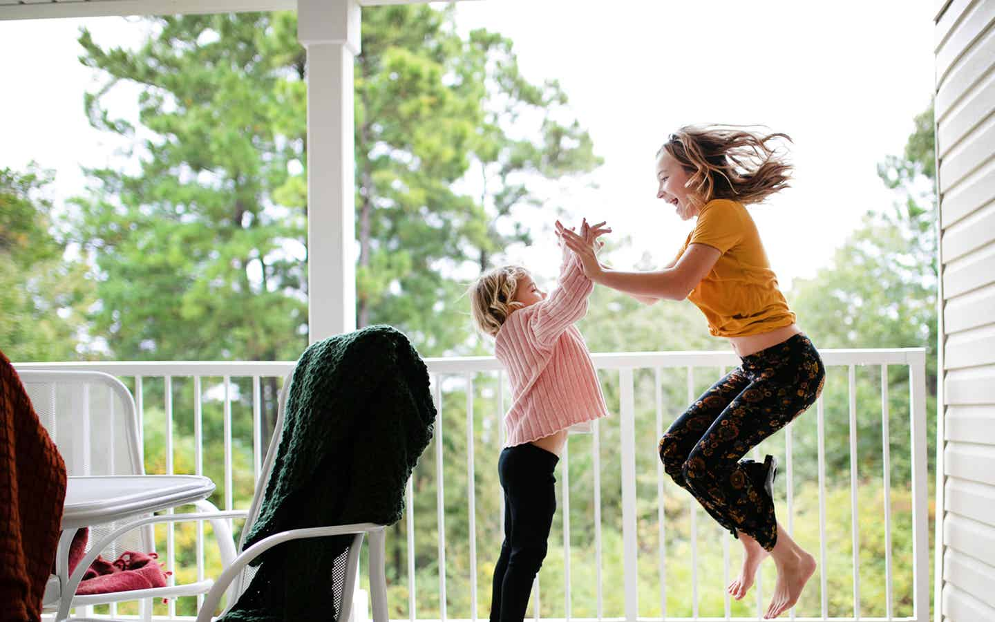 A mother and daughter dancing on a balcony at a resort