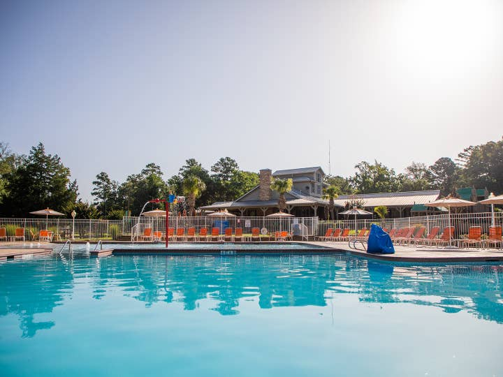 Outdoor springcreek pool surrounded by red pool chairs at Villages Resort in Flint, Texas
