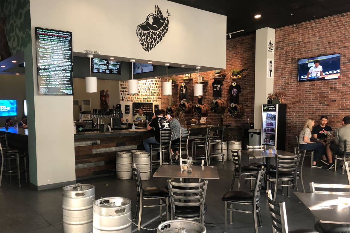 Interior of 'Tactical Brewing Co.' with various silver tables and kegs.