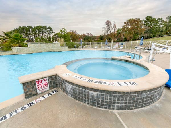 Hot tub attached to outdoor pool at Villages Resort in Flint, Texas.