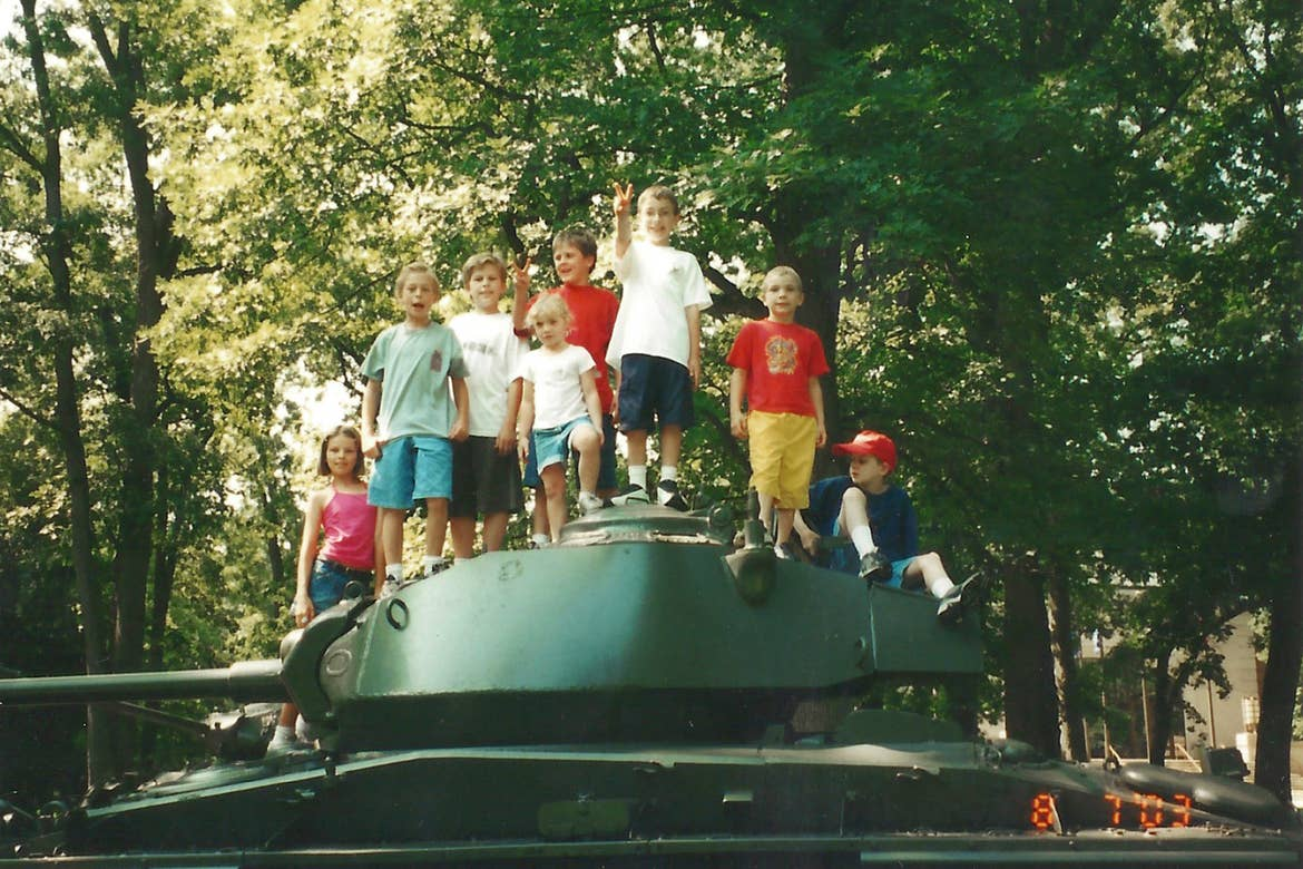 Several children stand on a retired US Army tank.